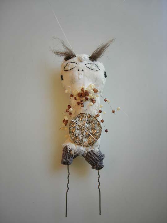 amulette 330 - textiles, perles, capsule métal monté sur jambes en épingles à cheveux